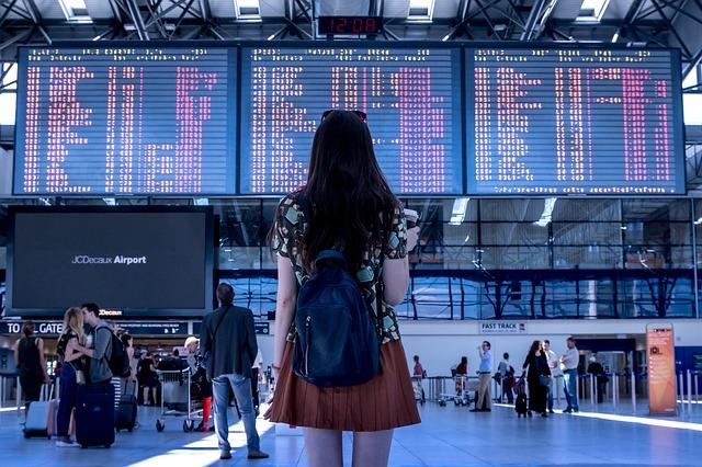 Femme regardant un panneau d'affichage de transport