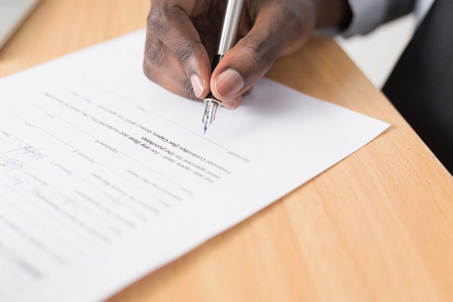 personne qui signe un papier pour résilier son contrat d'assurance automobile